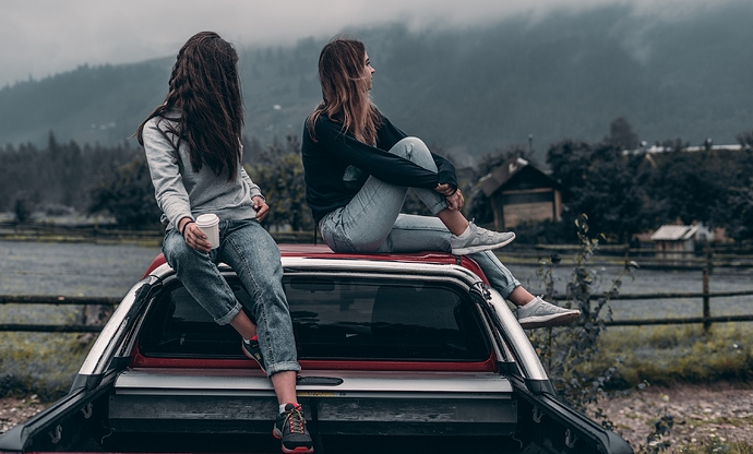 Canva%20-%20Two%20Women%20Sitting%20on%20Vehicle%20Roofs